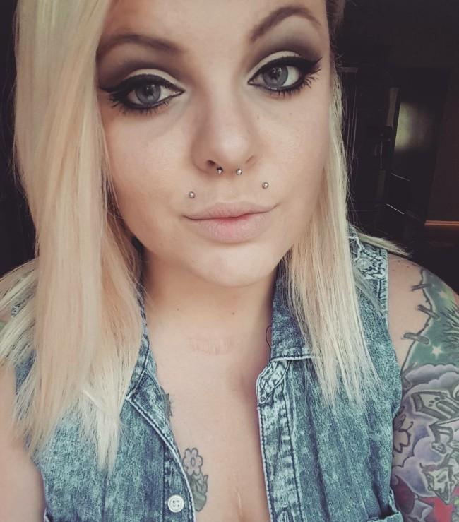 Piercing angel-bites y septum en mujer tatuada