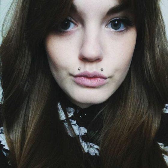 Piercing angel-bites en una mujer con cabello castaño