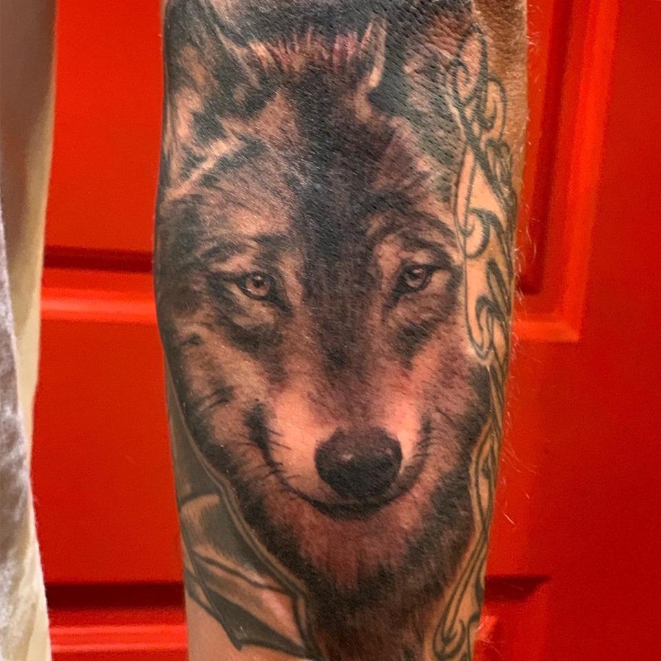 Tatuaje de lobo en el brazo en negro y gris por Kate Von D
