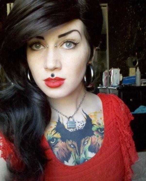 Piercing bridge y médusa en mujer tatuada