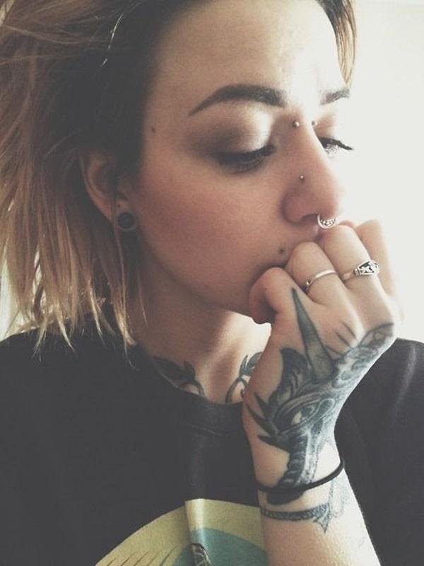 Piercing bridge y tatuaje en la mano