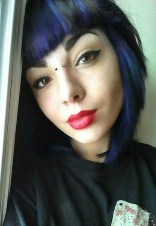 Piercing bridge en mujer con cabello castaño y azul