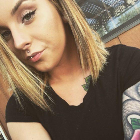Piercing jestrum en una chica con un tatuaje en el brazo