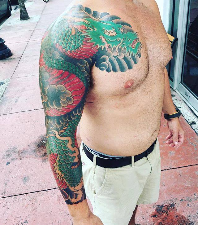 Tatuaje colorido brazo de dragón hecho por Ami James