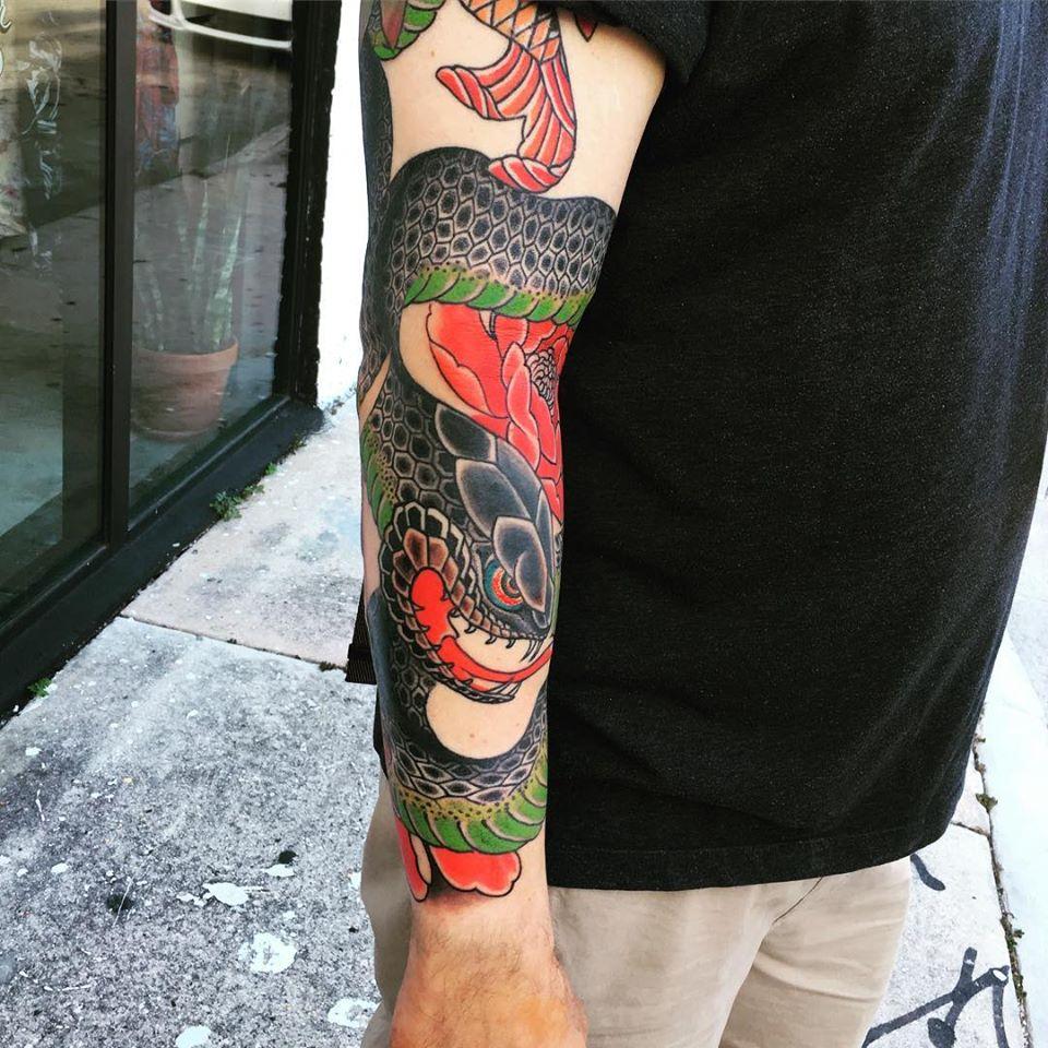 Colorido tatuaje de dragón en el brazo hecho por Ami James